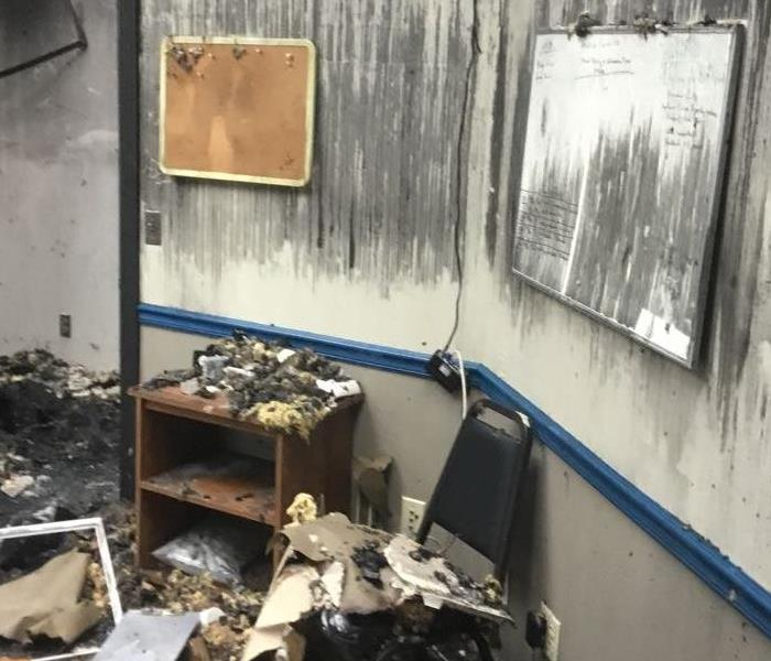 Two walls in an office with fire damage and burnt items