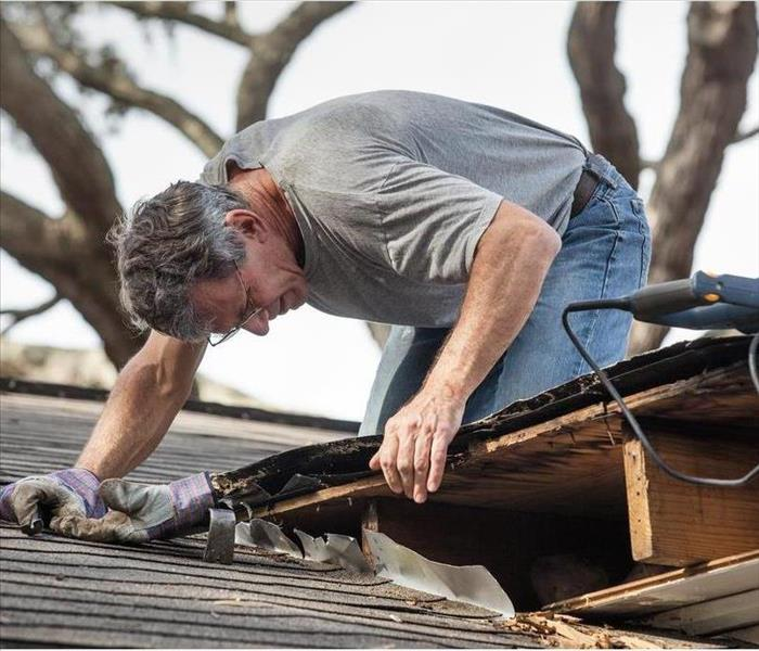A man inspecting roof