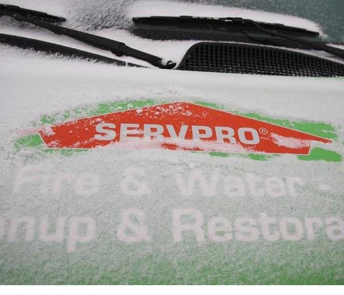 A vehicle covered in snow with a logo showing through