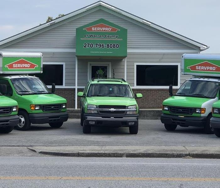 Here to Serve You. Image of SERVPRO vehicles outside of building.